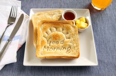 Slice of toast with Good Morning carved into it with butter and honey. photo