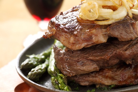 Fried onions on top of a stack of beef steaks. photo