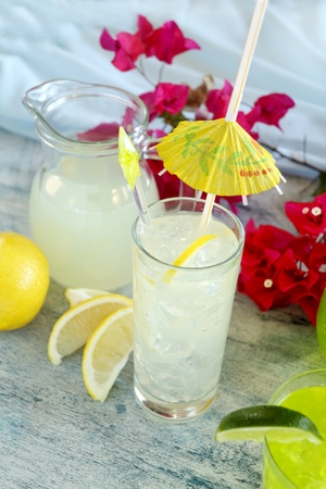 stirrer: Ice cold lemon drink with cocktail umbrella and stirrer.