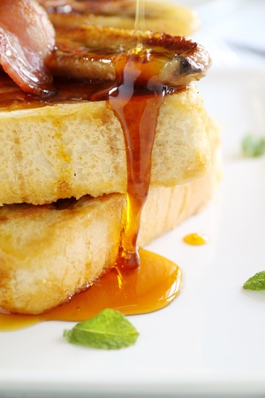 Maple syrup dripping down caramelized banana and french toast. photo