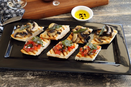 dips: A selection of finger food with mushrooms, tomato and onion including brushette and dips.