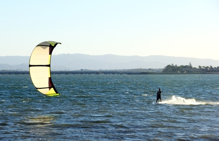 wakeboarding: Kite surfer speeding across the water at sunset. Stock Photo