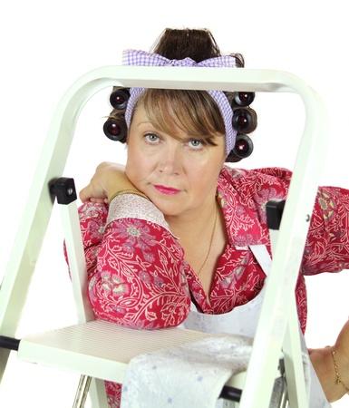 unconcerned: Frumpy ama de casa de mediana edad se apoya en una escalera contemplando la vida.