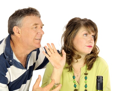 Unhappy middle aged couple having an argument with her ignoring him. photo