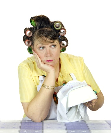 apathetic: Bored and apathetic housewife sick of wiping the dishes. Stock Photo