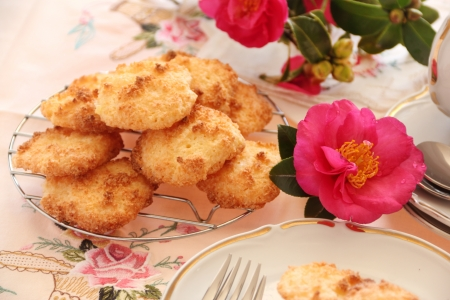 Fresh baked coconut macaroons ready to serve with a camellia. photo