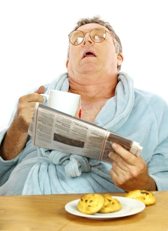 Nerdy middle aged man falls asleep at the breakfast table with a cup of tea and muffins. photo