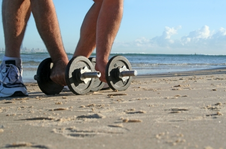 perspiring: Man picks up work out weights on the beach at sunrise.