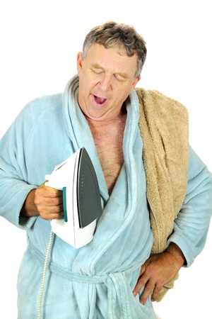 Yawning middle aged man in bath robe with iron.