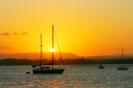 schooner: Yachts anchored at sunset with a blazing sun and sky  Stock Photo