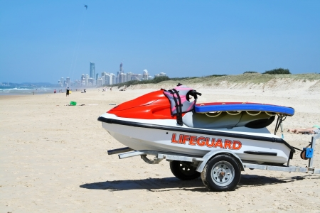 Lifeguard jet ski sits on the beach with Surfers Paradise in the background on the Gold Coast Australia  photo