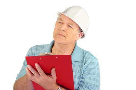 foremaster: Serious middle aged construction foreman with hard hat writing on clipboard.