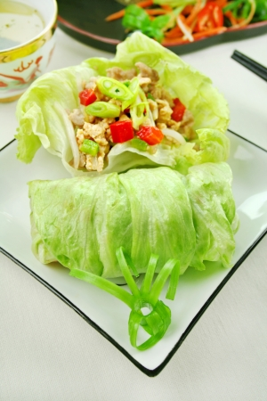 Delicious San Choy Bow with minced chicken and Chinese vegetables wrapped in fresh lettuce leaves. photo