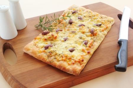 Rectangular gourmet pizza with cheese and olives ready to serve.