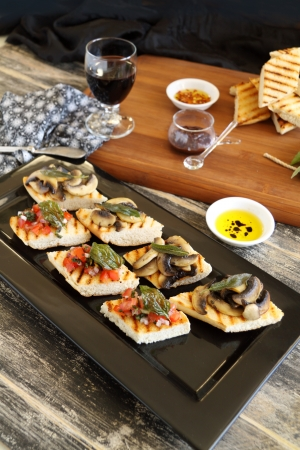 A selection of finger food with mushrooms, tomato and onion including brushette and dips. photo