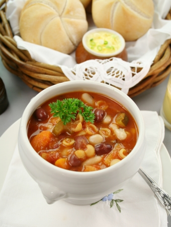 vegetable soup: Delicious minestrone soup with fresh baked bread rolls and butter. Stock Photo