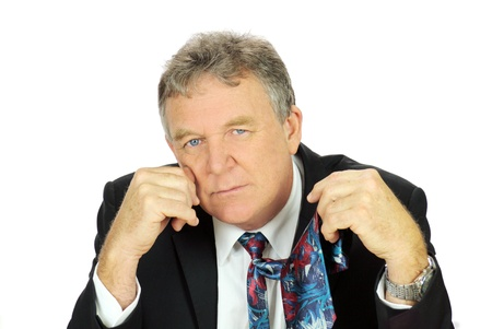 downhearted: Middle aged depressed businessman looking frustrated holding his tie.