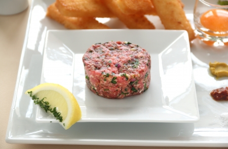 steak tartare: Steak tartare with raw egg in a glass ready to add to the beef. Stock Photo