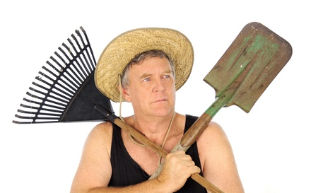 Serious middle aged gardener with straw hat holds a rake and spade. photo