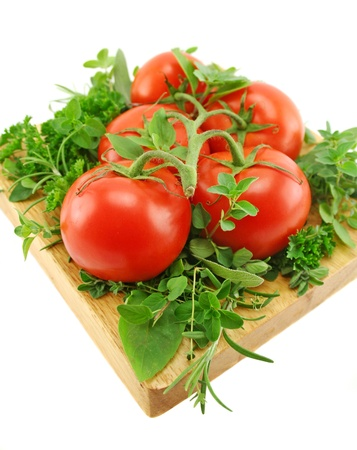 ripened: Vine ripened tomatoes on a bed of garden fresh herbs. Stock Photo