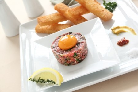 Delicious steak tartare with raw egg and condiments ready to serve. photo