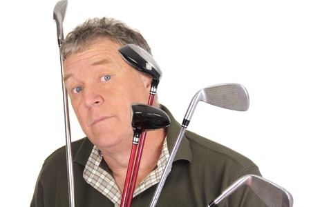 Middle aged golfer looking surprised through golf clubs  photo