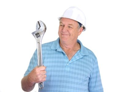 foremaster: Middle aged construction worker smiles looking at a large wrench.