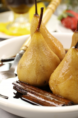 poached: Delicious poached pears with a cinnamon stick in syrup.