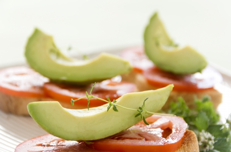 Delicious fresh slice of avocado with tomato and thyme on sliced toasts. Stock Photo - 18289202