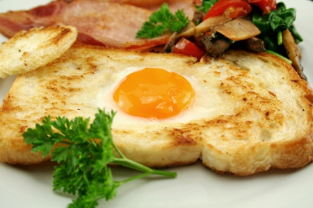 bacon and eggs: Egg embedded in toast with bacon, mushrooms, spinach and tomatoes.