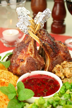 Roasted rack of lamb with red currant and mint sauce and potatoes with paprika and peas. Stock Photo - 18289199