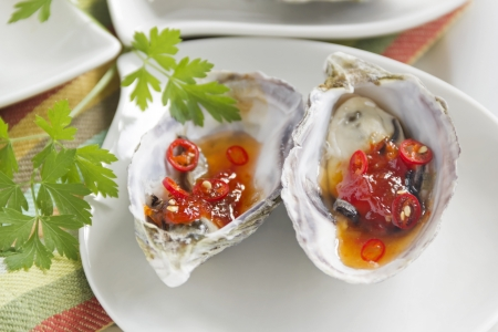 Delicious sweet chili oysters with parsley ready to serve. Stock Photo - 18652281