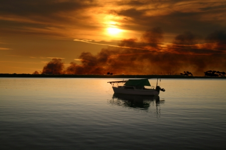 Sailing boat moored with a wild fire burning in the background  Stock Photo - 18652136