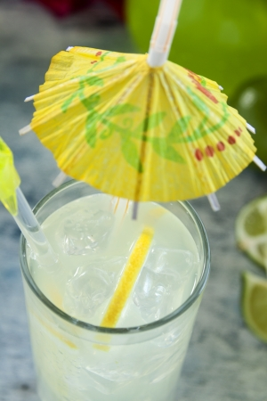 quenching: Delicious quenching lemon drink with ice and a cocktail umbrella.