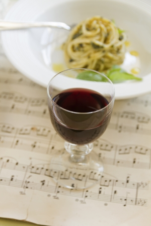 Red wine with pesto spaghetti on an old music sheet. photo