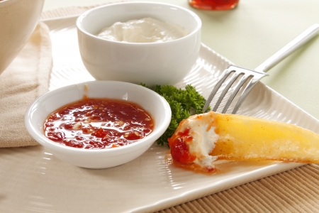 has been: A potato wedge that has been dipped with sour cream and sweet chili sauce. Stock Photo