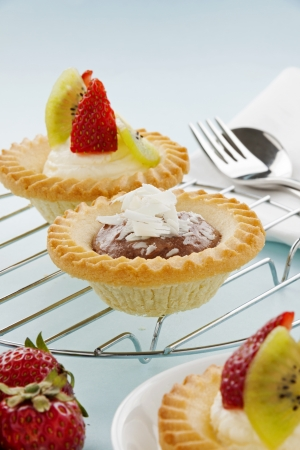 decadent: Delicious and decadent cream and chocolate tarts with fresh strawberries. Stock Photo