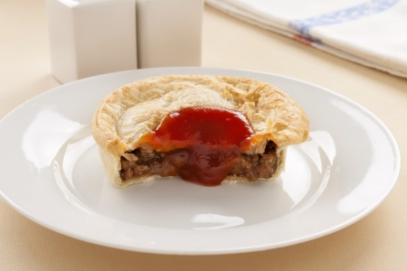 meat pie: Half eaten meat pie with ketchup dripping down the front. Stock Photo