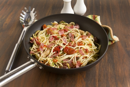Mediterranean salami spaghetti freshly cooked in a fry pan ready to serve. photo