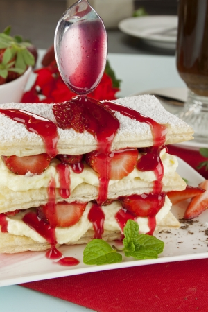 Delicious strawberry mille feuille with strawberry syrup being poured on top.