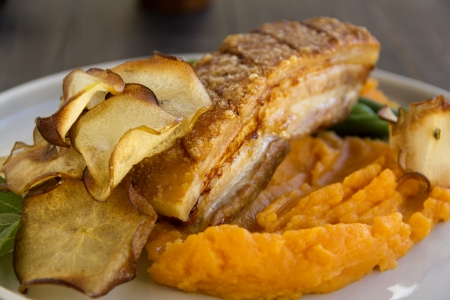crackling: Delicious roasted pork belly with crackling, fried apple crisps, sweet potato mash and steamed green beans.
