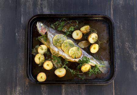 plato de pescado: Pasteler�a deliciosa trucha arco iris reci�n salido del horno con patatas, lim�n y hierbas. Foto de archivo