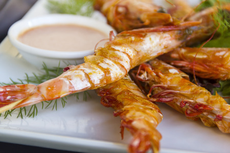 flavorful: Delicious grilled barbequed shrimps on skewers with a dipping sauce and fresh garden salad.