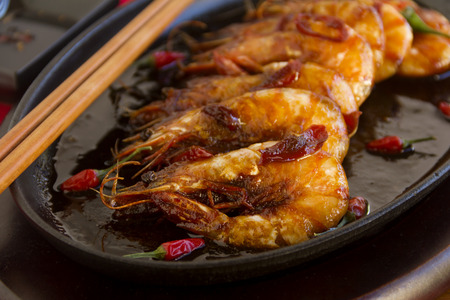 sizzling: Delicious Asian sizzling chilli shrimps served in a hot cast iron platter.