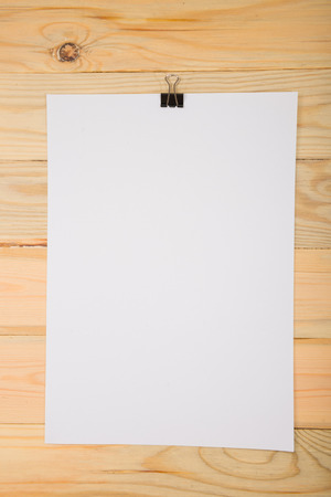 stack of files: Black clip and White blank note paper hang on wood pane