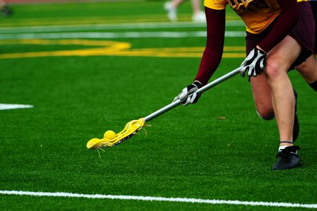 Womens lacrosse player scooping up the ball.