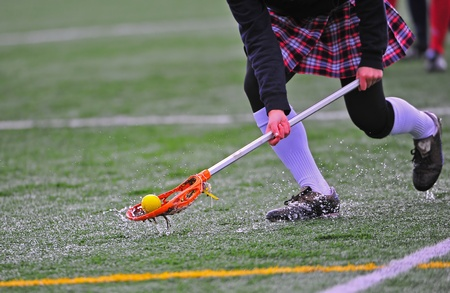 drenched: High school girls varsity lacrosse player scoops up the ball on a rain drenched turf field. Stock Photo