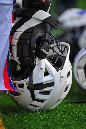Boys Lacrosse helmet and a gloved hand resting on a turf field