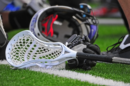 High school boys varsity lacrosse stick head laying on a turf field with a glove and helmet in the background.