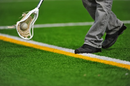 High school boys varsity lacrosse stick head catching a ball on a turf field as it goes out of bounds. Stock Photo